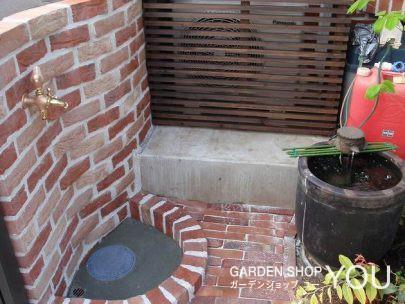 塀を兼ねた立水栓は優しくカーブを描いて。旧いお庭にあった水鉢がさりげないアクセント。