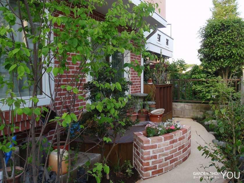 赤系レンガ主体のお庭に植栽が爽やかさを添えます。