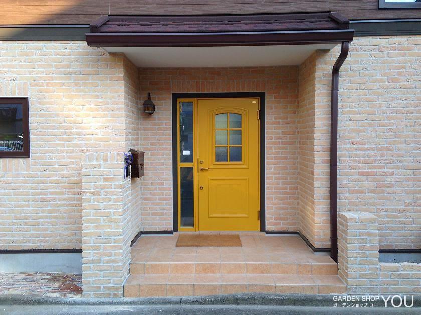 淡いレンガのシンプルな外構ゆえ、パッと目を引く黄色のドア