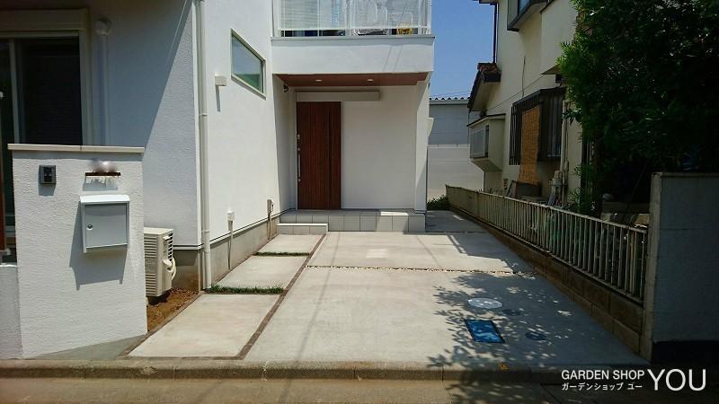 レンガで枠組みすることで駐車場との境界を表す玄関へのアプローチ。