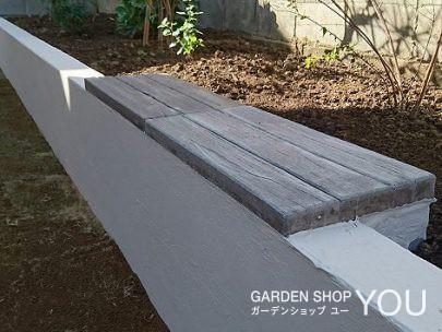 裏庭。緑の花壇をバックにくつろぐベンチ。