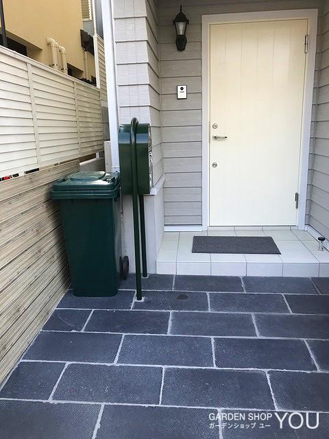 グレーの外構と真っ白な玄関ドア。