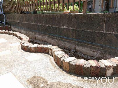 コンクリートをはつってレンガで土留めを。